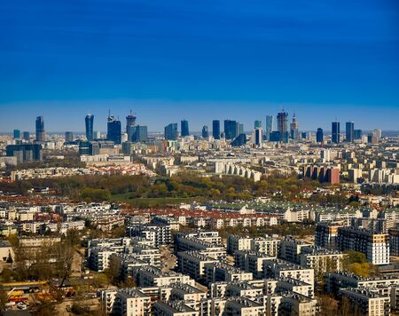 Beautiful panoramic aerial cityscape - view from the window of the plane landing at the center of Warsaw (Poland) with skyscrapers, with parks and residential areas, early spring at sunset