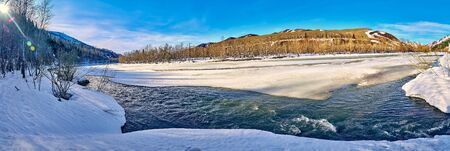 Panoramic aerial view: beautiful spring landscape: the Ulba river in Kazakhstan wakes up from winter sleep - ice drift - snow and ice are melting in the mountains, the bright sun is shining, Qazaqstan