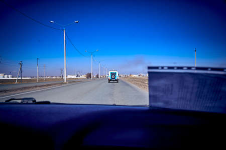 UST-KAMENOGORSK, KAZAKHSTAN - APRIL 11, 2020: police patrol car patrolling the road - strange and unusual view of the empty streets - all people are at home because of quarantine and pandemic, KZ
