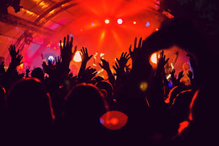 Abstract blur atmosphere: happy people enjoying outdoor music festival concert, raised up hands and clapping of pleasure, active night life concept, play of light and shadow on the huge stage
