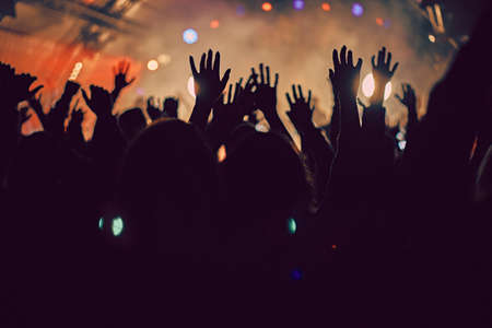 Abstract blur atmosphere: happy people enjoying outdoor music festival concert, raised up hands and clapping of pleasure, active night life concept, play of light and shadow on the huge stage 写真素材