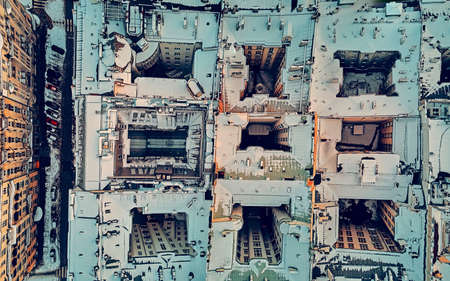 Beautiful panoramic aerial top-down drone view on snow-covered roofs of Warsaw 19th-century tenement houses during the January sunset, Warsaw, Poland.