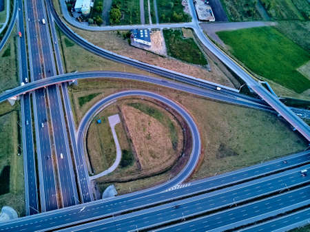 A beautiful panoramic aerial drone view of the sunset on the highway overpass of the southern Warsaw bypass (Polish: POW), Michalowice district in Warsaw, Opacz Kolonia, Poland