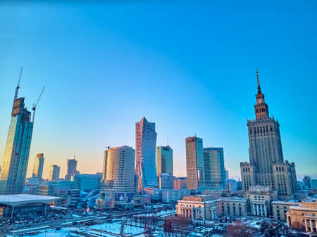 Beautiful panoramic aerial drone view on Warsaw City Skyscrapers, PKiN, and Varso Tower under construction and 19th-century tenement houses during the January sunset, Warsaw, Poland
