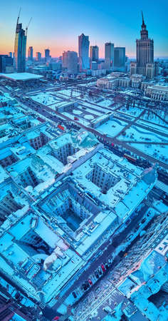 Beautiful panoramic aerial drone view on Warsaw City Skyscrapers, PKiN, and Varso Tower under construction and 19th-century tenement houses during the January sunset Редакционное