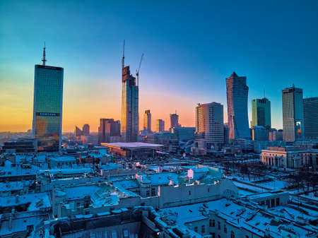 WARSAW, POLAND - JANUARY 31, 2021: Beautiful panoramic aerial drone view on Warsaw City Skyscrapers, PKiN, and Varso Tower under construction and 19th-century tenement houses during the January sunset