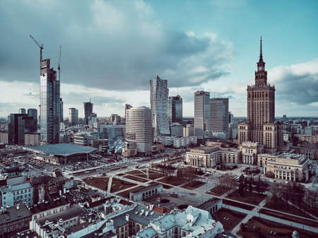 Beautiful panoramic aerial drone view on Warsaw City Skyscrapers, PKiN, and Varso Tower under construction and 19th-century tenement houses during the february sunset, Warsaw, Poland