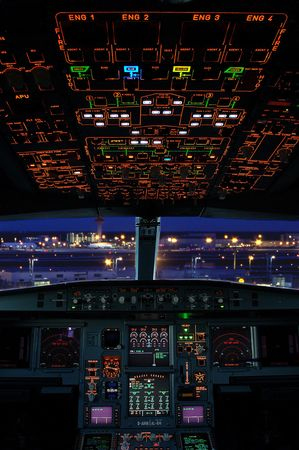 Airbus cockpit with airport scene at night.