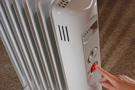 Electric radiator is switched on to heat the living room.