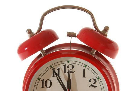 red alarm clock, five minutes to twelve.               photo