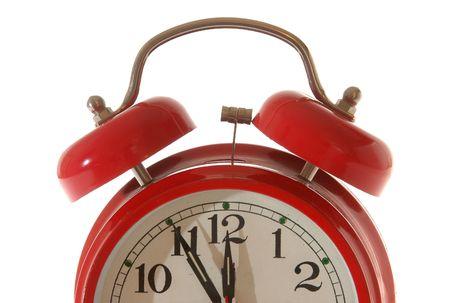 red alarm clock, five minutes to twelve.