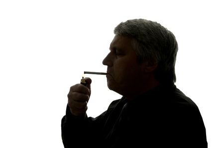 Man is smoking a cigarette, cigarette lighter in his hand.                                photo