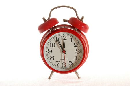 Red alarm clock shows five minutes to twelve. Stock Photo