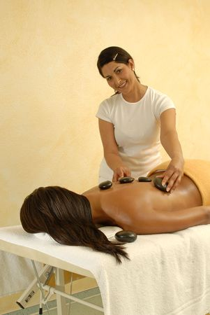 young woman getting hot stone massage therapy. Stock Photo