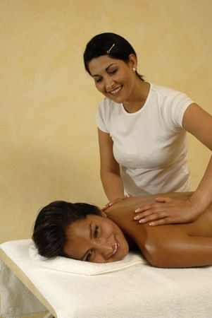 young woman getting massage therapy.Masseur and client smiling.