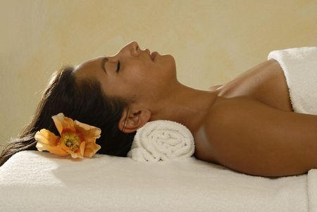 Young woman relaxing,lying on a massage table.Spa area.