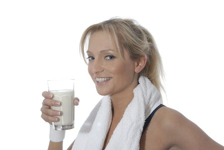 Young woman drinking a glass of milk.Isolated over white,wearing sporting outfit. Stock Photo