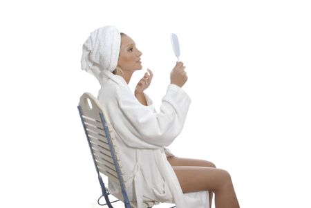 Woman in spa area is taking care of her face.Wearing robe and turban. Stock Photo