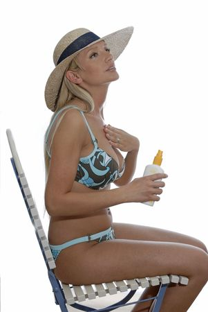 sun lotion: Young girl wearing bikini applying sun lotion. Sitting on a chair. Stock Photo