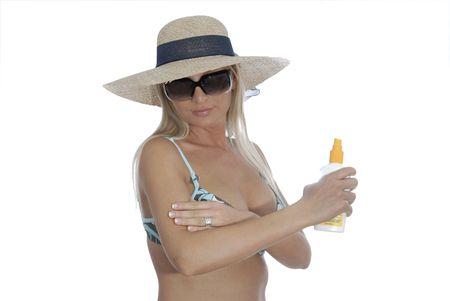 Bikini Girl applying sun lotion. Wearing a straw hat and sunglasses.
