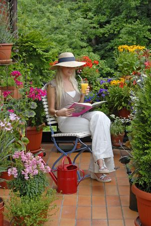 terrace: Young woman enjoying her free time on a  balcony with flowers. Stock Photo