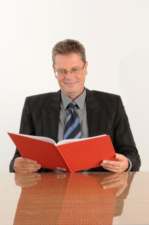Business man at the office, reading company figures. Red book in his hand.