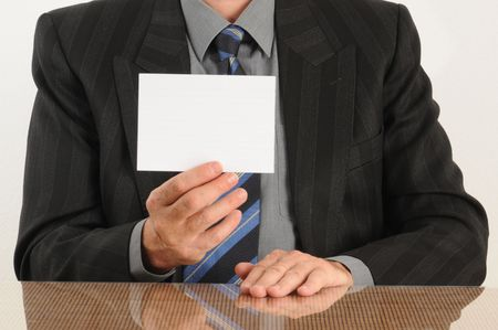 Business man holding a blank card in hand, wearing jacket and tie.