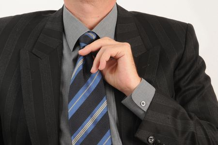 Business man adjusts his tie. Isolated over white.