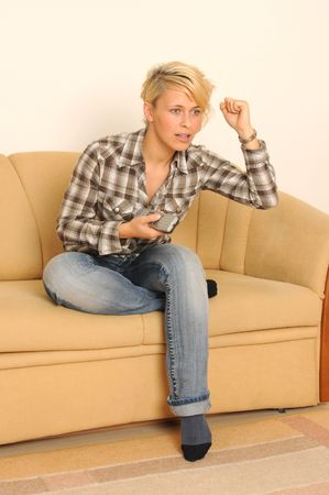Young woman sitting on a couch watching TV. Stock Photo