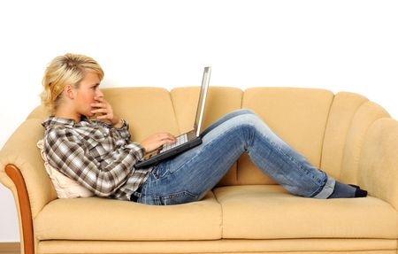 Young woman working with her laptop, sitting on a sofa.