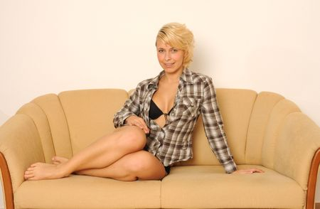 Sexy young woman,wearing a brown blouse and black lingerie.Lying on a couch. photo