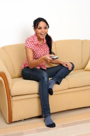 woman watching tv: Young woman watching TV.