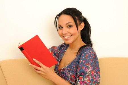 young woman at home, reading a book. Stock Photo