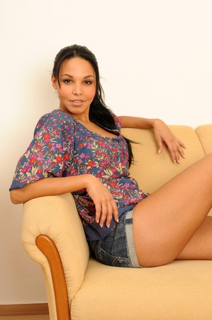 young woman at home, sitting on a couch.