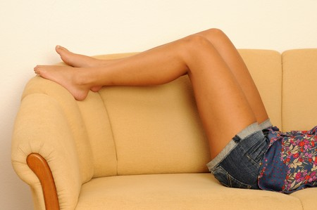 young woman at home, lying on a couch.