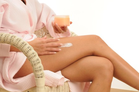 young woman applying body lotion. Stock Photo