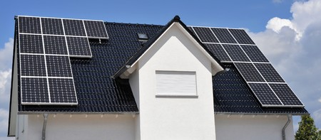 roofing system: A dark tile roof with solar panels Stock Photo