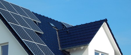 A dark tile roof with solar panels Stockfoto