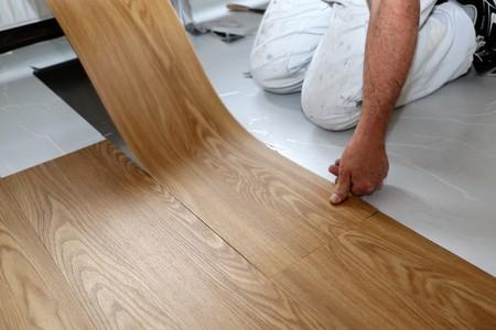 Man laying PVC floor Foto de archivo