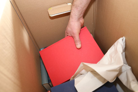 Laying books into a moving box Stock Photo