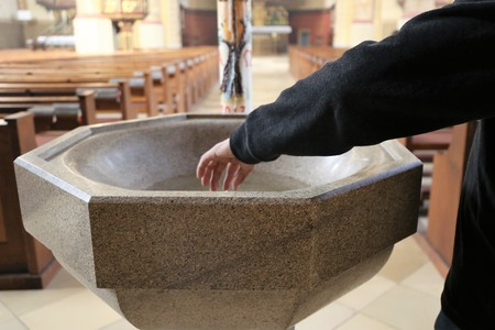 Devout Christian dipping his fingers in holy water