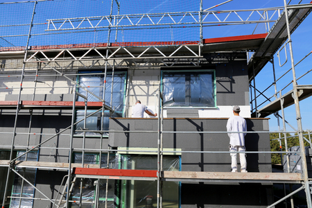 Construction workers yield house facade Editorial