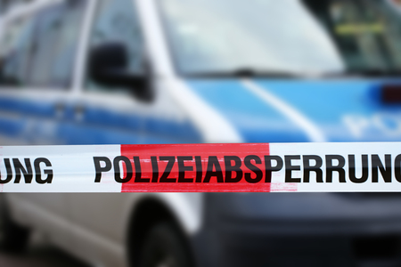 Police cordon tape with a police car in the background (Germany) 스톡 콘텐츠