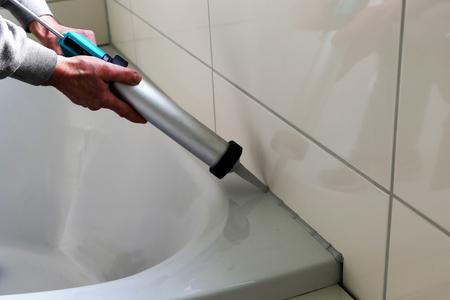 Man sealing a bath or basin with silicone
