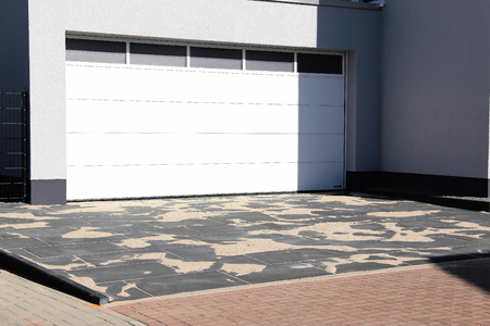 Modern paved house entrance with white garage door