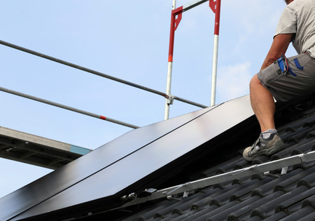 Worker installing a photovoltaic system