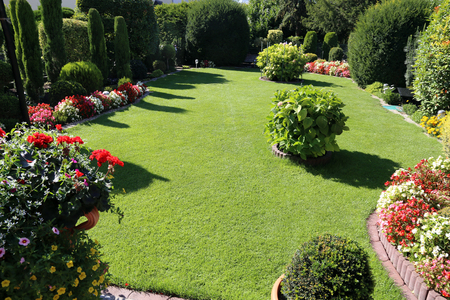 Neat and tidy garden with turf and flowers Stock Photo
