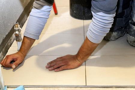 Travailleur pose des carreaux de sol Banque d'images