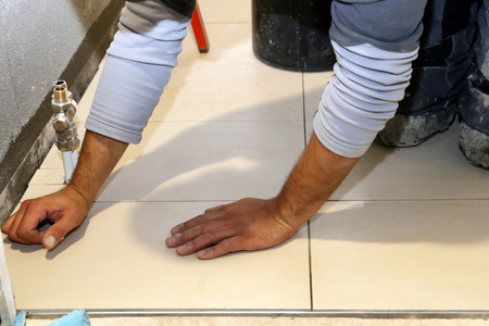 Worker laying floor tiles Banque d'images