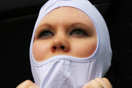 Female race car driver putting on her balaclava
